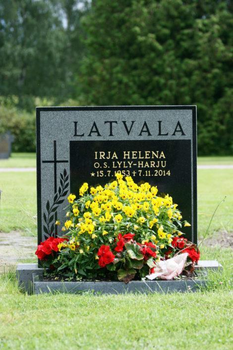 Muistomerkissä on hiekkapuhallettu sukunimen ja ristin tausta, jolloin teksti ja kuva jää koholle kiven pinnasta.