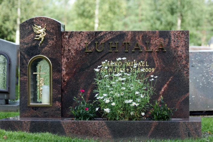 Kuvan hautakivessä kaikki näkyvät sivut on hiottu. Pronssituotteet ovat kullattuja