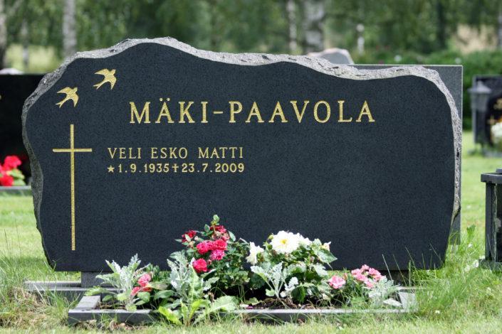 Hautakivi on musta mattapintainen. Nimen tila on vierellä ja alle mahtuu tarvittaessa lisää nimiä