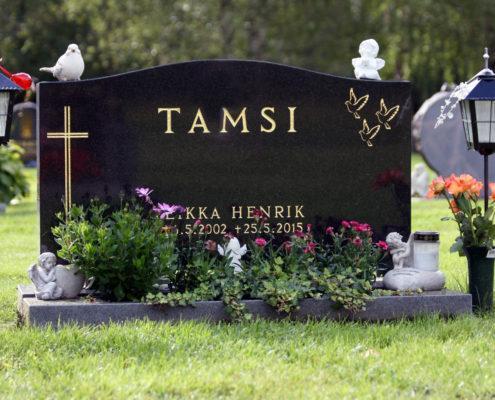 Kaareva hautakivi, jossa koristeet ja tekstit ovat kullattu