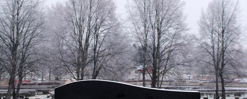 Päältä kaareva hautakivi lyhtykehyksellä ja kullatuilla kaiverruksilla