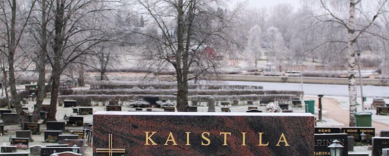 Mäntsälän punainen hautakivi kullatuilla kaiverruksilla ja koristeilla. Kukille on tehty erilliset reunukset kivistä