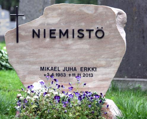Kauniin mallinen hautakivi luonnonkivestä. Kivi on jätetty edestä sahatuksi.